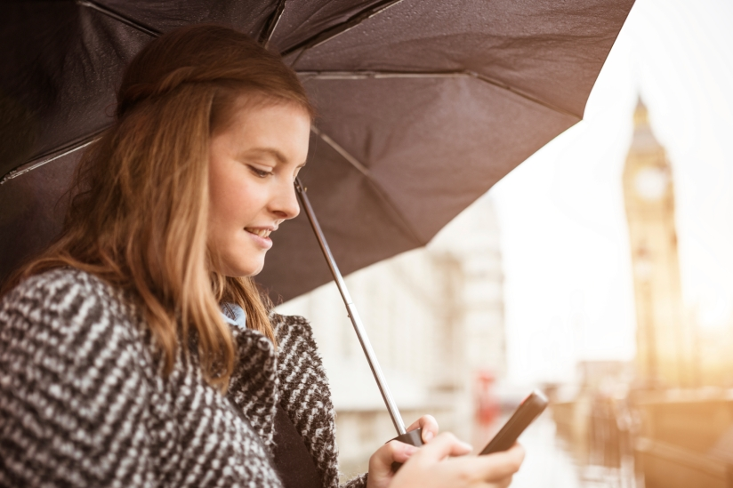 Woman holding umbrella and using smartphone.